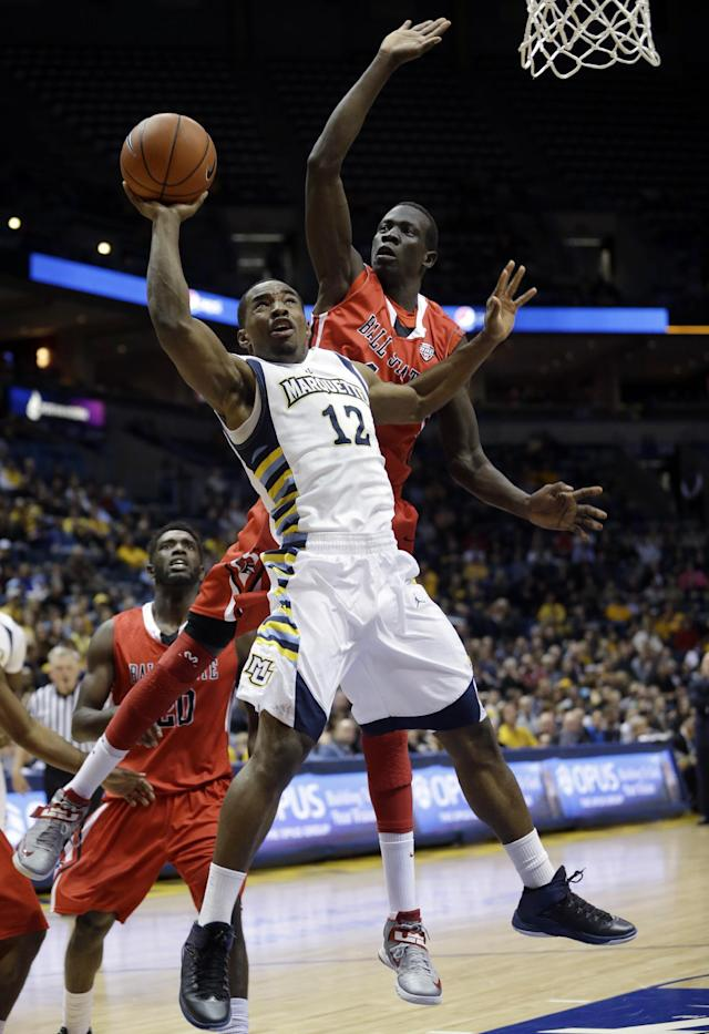 Marquette's Derrick Wilson shoots in front of Ball State's Mading Thok during the first half of an NCAA college basketball game Tuesday, Dec. 17, 2013, in Milwaukee. (AP Photo/Morry Gash)