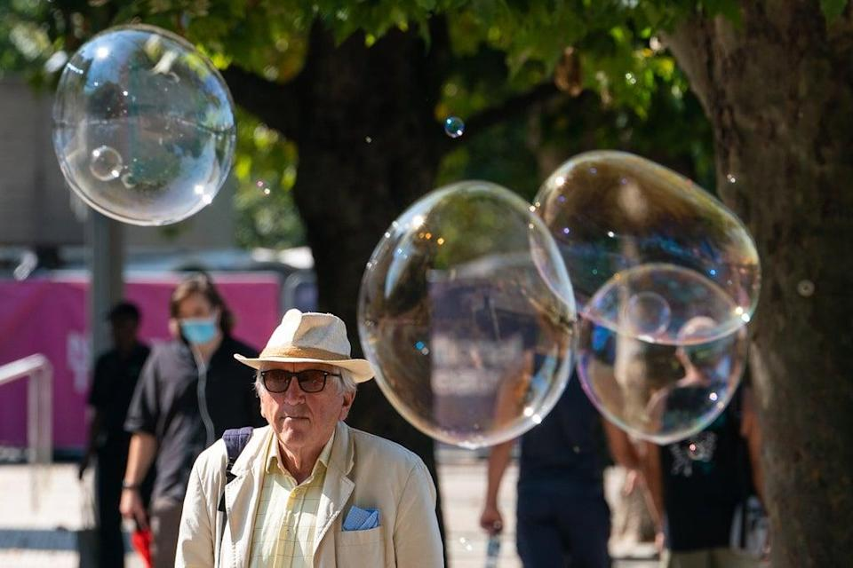 A man walks among giant bubbles from a street performer on the South Bank, London (Dominic Lipinski/PA) (PA Wire)