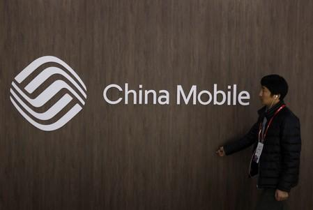 A man walks past the China Mobile logo at the Mobile World Congress in Barcelona