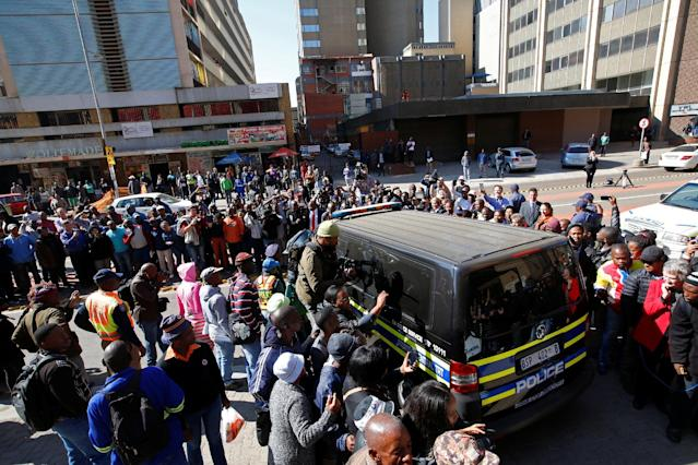 Journalists crowd around a van believed to be carrying Olympic and Paralympic track star Oscar Pistorius after his sentencing at the North Gauteng High Court in Pretoria, South Africa, July 6, 2016. REUTERS/Mike Hutchings