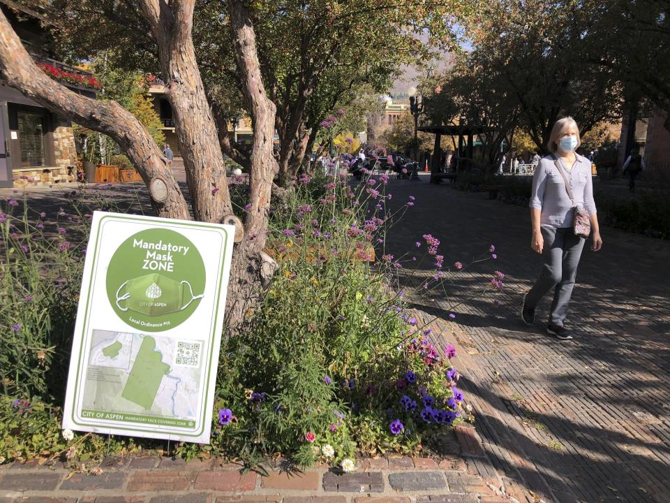 In this Oct. 3, 2020 photo, a pedestrian walks past one of the many signs along the mandatory mask zone in the downtown area in Aspen, Colo. Aspen has taken numerous precautionary measures during the coronavirus pandemic, including mask mandates, occupancy limits in shops and restaurants, and social distancing. (AP Photo/John Marshall)