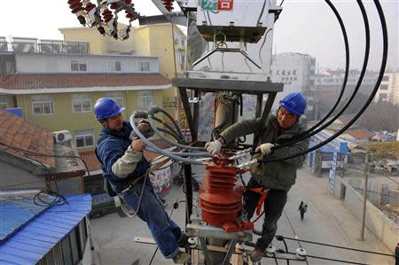 Technicians conduct maintenance work on a utility pole in Changtian, Anhui province