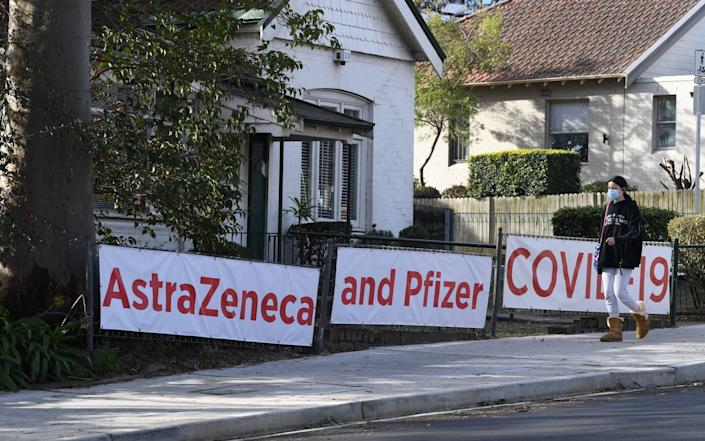 People pass a doctor's surgery offering both the Astra Zeneca and Pfizer vaccine in a suburb of locked down Sydney, Australia - James D. Morgan/Getty Images