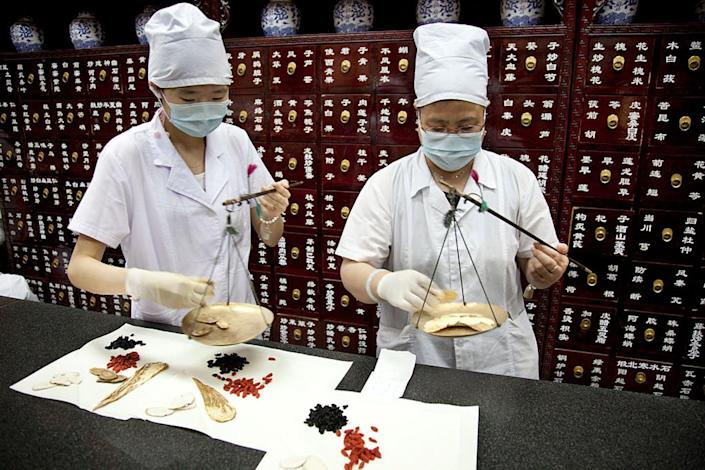 Two traditional Chinese medicine practitioners weigh and wrap herbs at Tong Ren Tang.