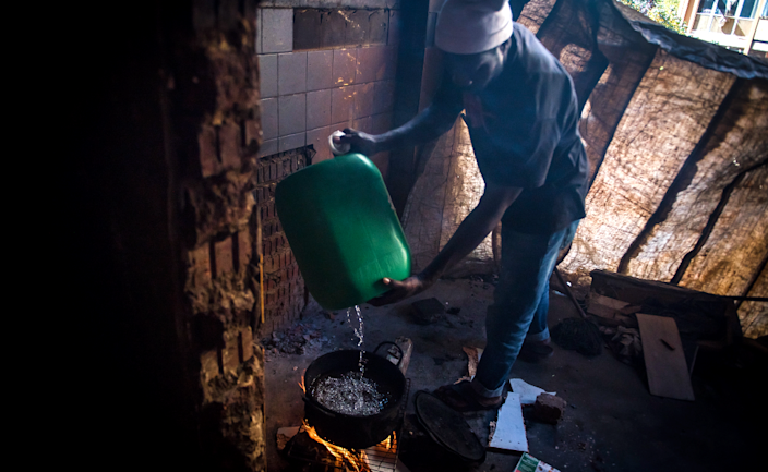 An unknown man pours water from a container into a pot over an open fire in preparation of cooking a meal in the derelict San Jose building in Johannesburg, South Africa
