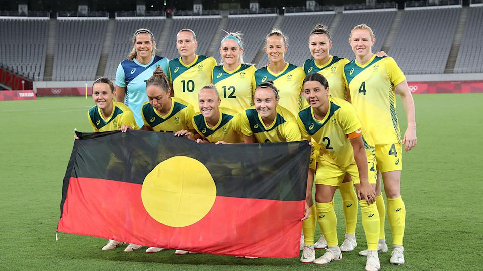 Pictured here, the Matildas squad poses with the Aboriginal flag before a match at the Tokyo Olympic Games.