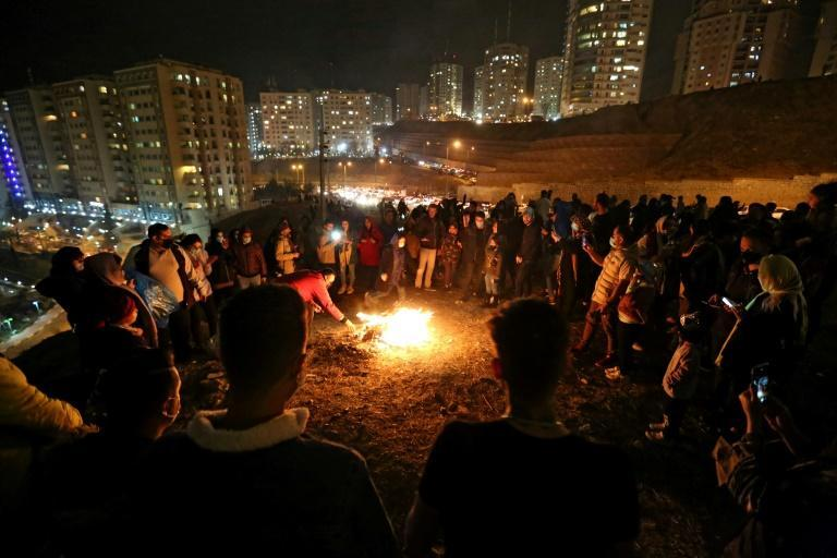 Iranian families gather round a bonfire in Tehran, ignoring a ban on gatherings in the capital, to celebrate Chaharshanbe Suri, the fire festival held in the runup to this weekend's Persian New Year