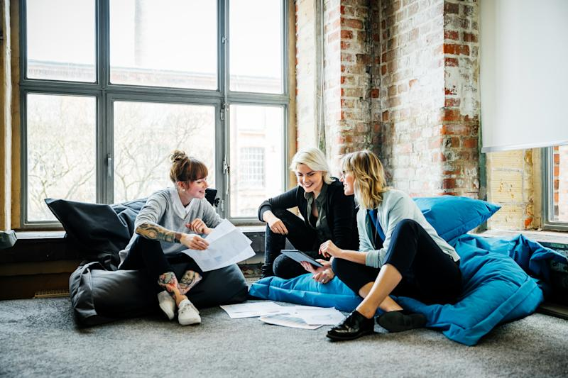Three businesswomen sitting on large Pillows in an office and talking during an informal meeting