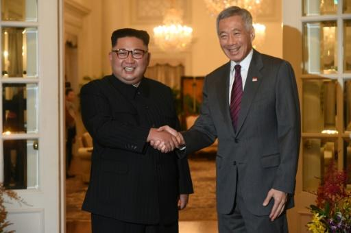North Korea's leader Kim Jong Un (L) is welcomed by Singapore's Prime Minister Lee Hsien Loong