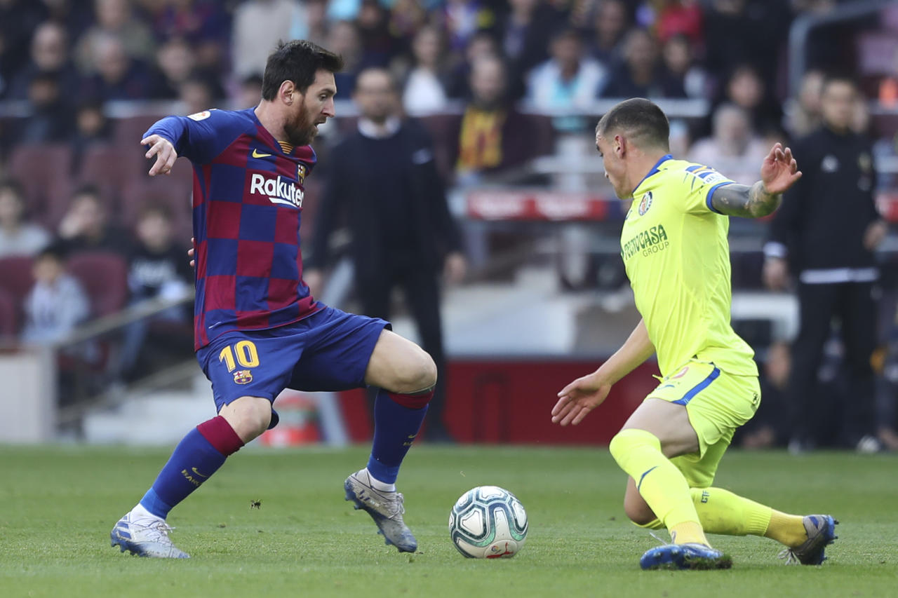 Barcelona's Lionel Messi, left, takes on Getafe's Mauro Arambarri during a Spanish La Liga soccer match between Barcelona and Getafe at the Camp Nou stadium in Barcelona, Spain, Saturday Feb. 15, 2020. (AP Photo/G.Garin)