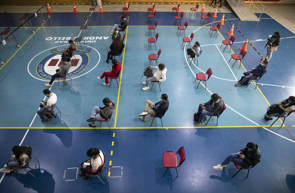 """<span class=""""caption"""">University students wait to be vaccinated at Andres Bello University in Santiago, Chile, in June 2021.</span> <span class=""""attribution""""><span class=""""source"""">(AP Photo/Esteban Felix) </span></span>"""