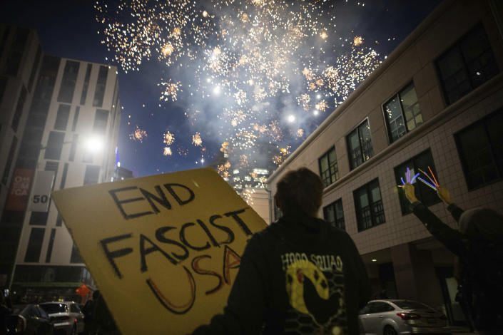 Protesters light fireworks in the middle of downtown Oakland during a protest on Saturday, July 25, 2020, in Oakland, Calif. Protesters in California set fire to a courthouse, damaged a police station and assaulted officers after a peaceful demonstration intensified late Saturday, Oakland police said. (AP Photo/Christian Monterrosa)