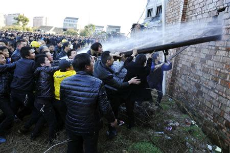 People try to break through the wall for firefighters to extinguish a fire at a factory in Wenling
