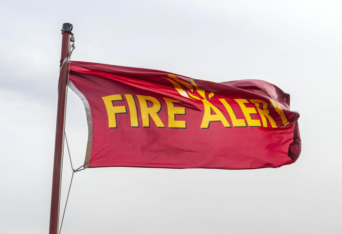 A fire alert flag flies in strong Santa Ana winds at the intersection of Silverado Canyon Road and Santiago Canyon Road in Silverado, Calif., early on Tuesday afternoon, Jan. 19, 2021, as winds picked up throughout Orange County and Southern California. (Mark Rightmire/The Orange County Register/SCNG via AP)
