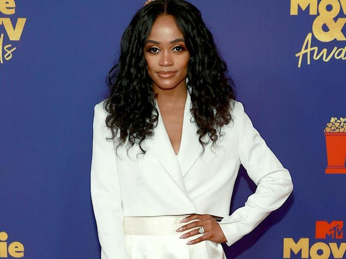 """""""Bachelorette"""" star Rachel Lindsay poses in a white suit while on the red carpet of the 2021 MTV Movie and TV Awards."""
