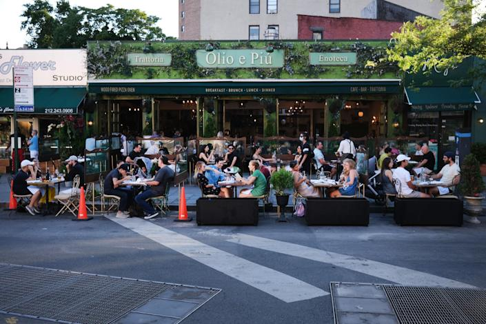 Guests dine at tables outside of a Manhattan restaurant during the summer.