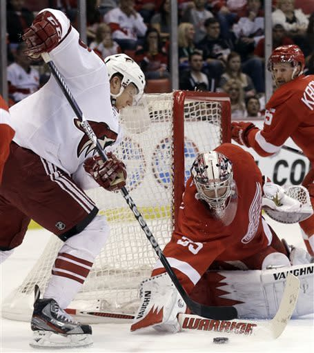 Detroit Red Wings goalie Jimmy Howard (35) stops a shot by Phoenix Coyotes wing Rob Klinkhammer, left, in the first period of an NHL hockey game in Detroit, Monday April 22, 2013. (AP Photo/Paul Sancya)