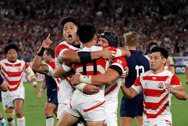 Japan's Kenki Fukuoka is congratulated by his teammates after scoring his team's third try during the Rugby World Cup Pool A game at International Stadium between Japan and Scotland in Yokohama, Japan, Sunday, Oct. 13, 2019. (AP Photo/Christophe Ena)