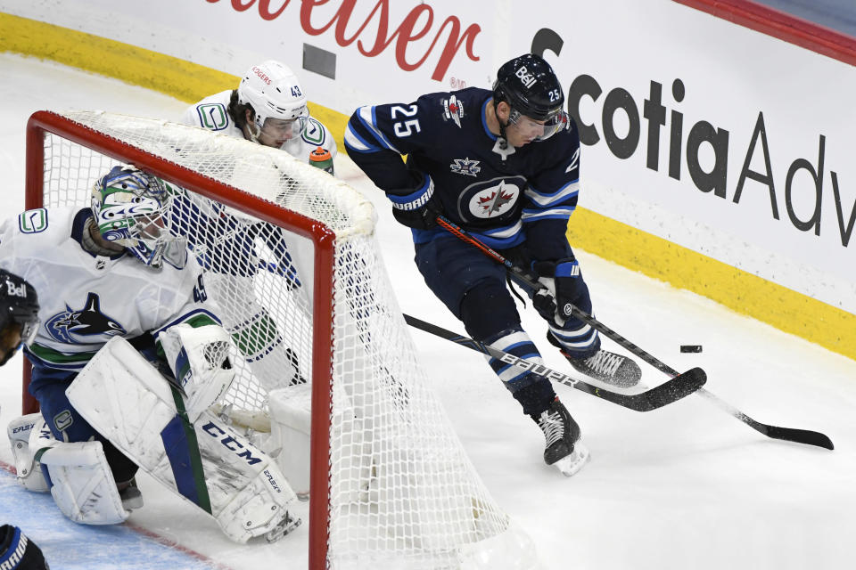 Winnipeg Jets' Paul Stastny (25) carries the puck around Vancouver Canucks' Quinn Hughes (43) during the second period of an NHL hockey game Tuesday, May 11, 2021, in Winnipeg, Manitoba. (Fred Greenslade/The Canadian Press via AP)