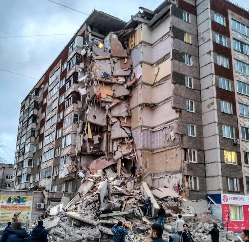 Passers-by look at a partially collapsed nine-storey residential building in Izhevsk following a suspected gas explosion