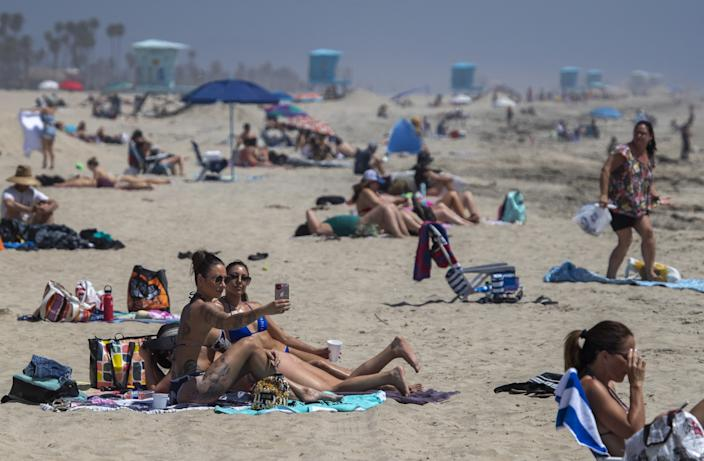 Cailin Healy and an unidentified friend, both of Calabasas, take a selfie together as beachgoers enjoy warm summer-like weather in Huntington Beach amid state and city social distancing regulations mandated by Gov. Newsom.