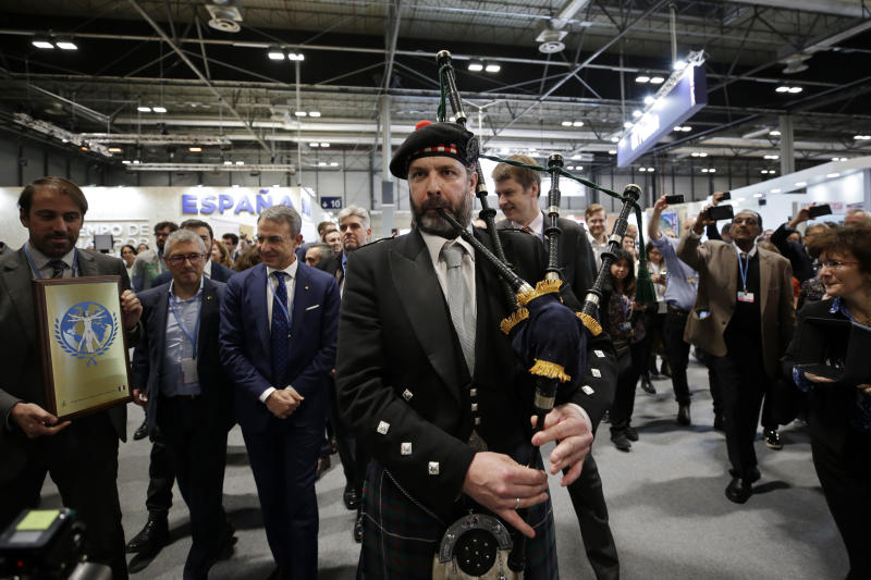 A bagpipe player accompanies a UK delegation to promote COP26 to be held in Glasgow, at the COP25 climate talks congress in Madrid, Spain, Friday, Dec. 13, 2019. (AP Photo/Paul White)