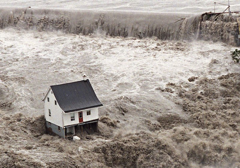 <p>On July 21, 1996, a white house resists being swept away by floodwaters in the Saguenay region of Quebec in an image considered to be symbolic of the devastation in the area at the time. Photo from The Canadian Press. </p>