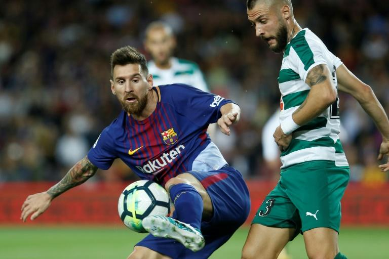 Barcelona's Lionel Messi (L) vies with Eibar's David Junca during their match in Barcelona on September 19, 2017
