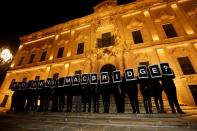 """FILE PHOTO: Activists from Occupy Justice Malta hold up placards reading """"Who Owns Macbridge?"""" in reference to revelations by the Daphne Project, outside the office of Prime Minister Joseph Muscat at Auberge de Castille in Valletta"""
