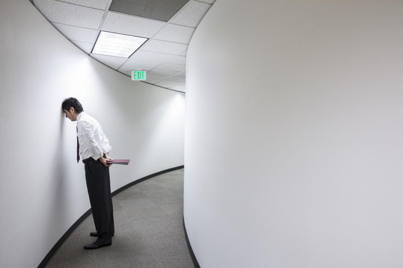 An Asian businessman frustrated and standing with his head against a wall in a hallway.