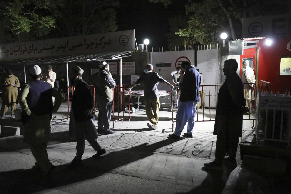 Afghans wait outside the hospital to see their relatives in Kabul, Afghanistan, Friday, April 30, 2021. A powerful suicide truck bombing struck a guest house in eastern Afghanistan on Friday, killing at least 14 people and wounding as many as 90, the Interior Ministry said. (AP Photo/Rahmat Gul)