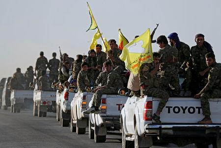 Fighters of Syrian Democratic Forces ride on trucks as their convoy passes in Ain Issa