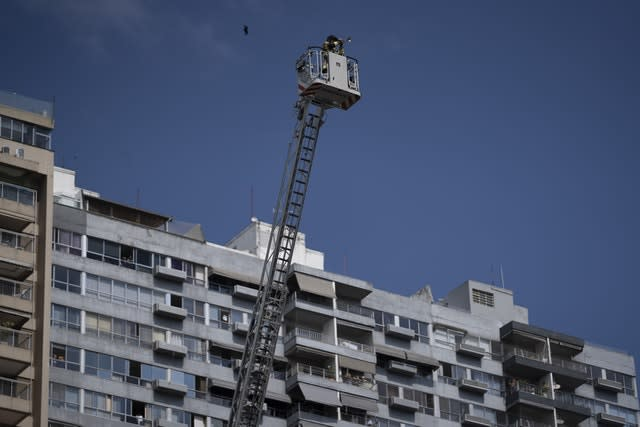 Firefighter Elielson Silva plays his trumpet on the top of a ladder for residents stuck at home, during lockdown in Rio