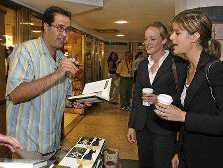 """In this photo provided by Subway, Jared Fogle (L), signs a copy of his new book """"Jared, The Subway Guy"""" for Alex Moser (C) and Gigi Garmendia (R) outside a Subway Restaurant in Rockefeller Center, New York City, August 21, 2006. REUTERS/Subway/Ray Stubblebine/HO"""