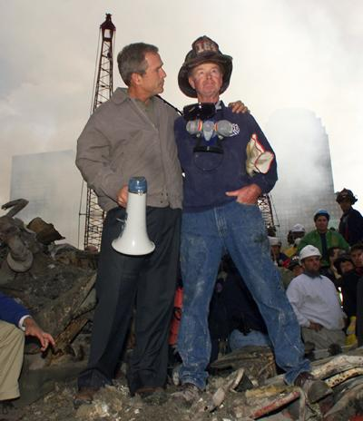 President George W. Bush embraces firefighter Bob Beckwith while standing in front of the collapsed World Trade Center buildings in New York on September 14, 2001. (AP Photo/Doug Mills)