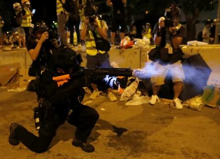 A police officer fires a baton round outside the Legislative Council building, after protesters stormed the building on the anniversary of Hong Kong's handover to China in Hong Kong