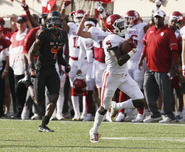 Oklahoma wide receiver Marquise Brown (5) takes off down the field in front of Oklahoma State cornerback A.J. Green (4) for a touchdown in the first half of an NCAA college football game in Stillwater, Okla., Saturday, Nov. 4, 2017. (AP Photo/Sue Ogrocki)
