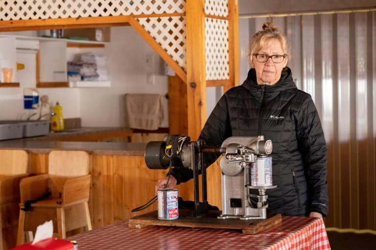 """Denise Gregoire stands ready to crimp syrup cans at the Constantin Gregoire Sugar shack in Saint-Esprit, Quebec on March 31, 2020.""""For me, this represents a shortfall of between 80,000 and 100,000 dollars,"""" laments Simon Lanoue, a maple syrup producer in Canada's Quebec province hit hard by measures to slow the spread of the new coronavirus"""
