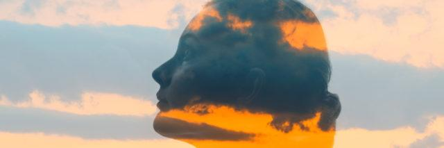 Double exposure of woman's face and sunset.