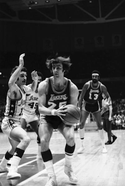Gail Goodrich (25) of the Los Angeles Lakers has his hair standing out from his head as he drives toward first period field goal try past blocking efforts of Dave Wohl (13) of the Philadelphia 76ers in Lakers Sixers NBA game on Friday, Jan. 14, 1972 in Philadelphia.Jerry West, Wilt Chamberlain and Goodrich were a Big Three to rival what Miami has, the core of a team that racked up routs on the way to an NBA-record 33 straight victories in the 1971-72 season. (AP Photo/WGI)