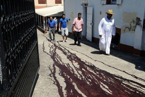 People pass by traces of pig's blood on the ground in front of the Montauban's mosque