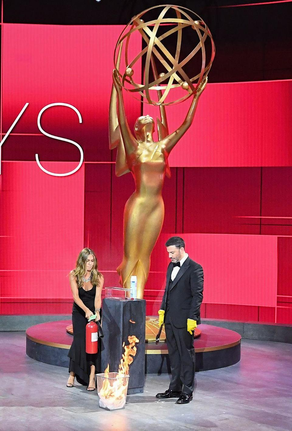 """<p>During a bit, Emmys' host Jimmy Kimmel started a fire that <a href=""""https://www.marieclaire.com/culture/a34089878/jennifer-aniston-emmys-little-black-dress/"""" rel=""""nofollow noopener"""" target=""""_blank"""" data-ylk=""""slk:presenter and nominee Jennifer Aniston"""" class=""""link rapid-noclick-resp"""">presenter and nominee Jennifer Aniston</a> had to help put out—only the fire didn't want to go out so easily, forcing the duo to battle some unexpectedly large flames. </p>"""