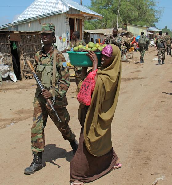 """In this photo of Sunday, May 27, 2012, A African Union soldier patrols the street in Afgoye town, Somalia, as a woman takes fruits to the market. Farmers from the Somali town of Afgoye, an al-Shabab stronghold until last week, filled their trucks with produce and drove across what used to be the frontline between government troops and insurgents. Farmers are rejoicing at the African Union's latest success: They will no longer have to pay 50 percent in """"taxes"""" to militants. (AP Photo/Farah Abdi Warsameh)"""