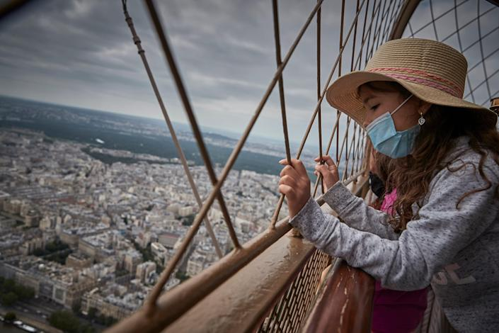 A girl looks down at Paris from the top of the Eiffel Tower as the iconic landmark reopened for the first time in over 8 months on July 16, 2021.