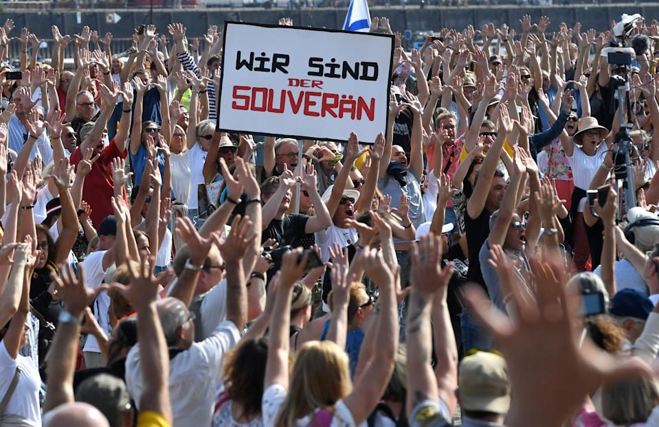 20 September 2020, North Rhine-Westphalia, Duesseldorf: Participants of a demonstration protest with signs on the Rhine meadows against the measures to combat the coronavirus. Photo: Roberto Pfeil/dpa (Photo by Roberto Pfeil/picture alliance via Getty Images)