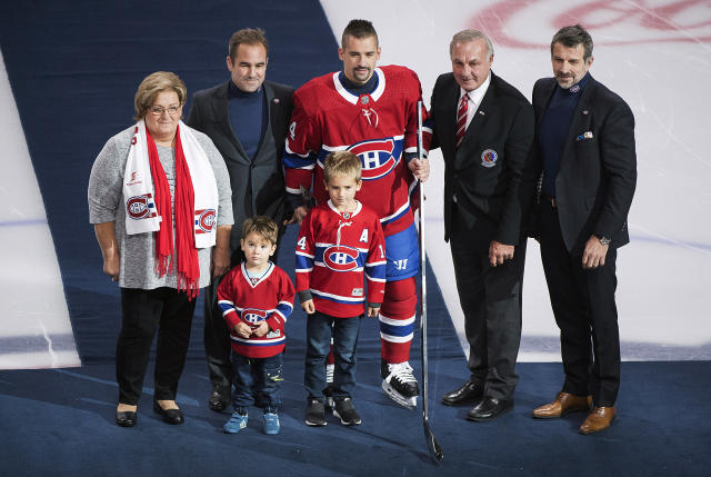 Montreal Canadiens' Tomas Plekanec, center, poses with family members and team owner Geoff Molson, second left, hockey great Guy Lafleur, second right, and Canadiens general manager Marc Bergevin during a ceremony to mark his 1,000th NHL hockey game prior to a game between the Canadiens and St. Louis Blues, in Montreal, Wednesday, Oct. 17, 2018. (Graham Hughes/The Canadian Press via AP)