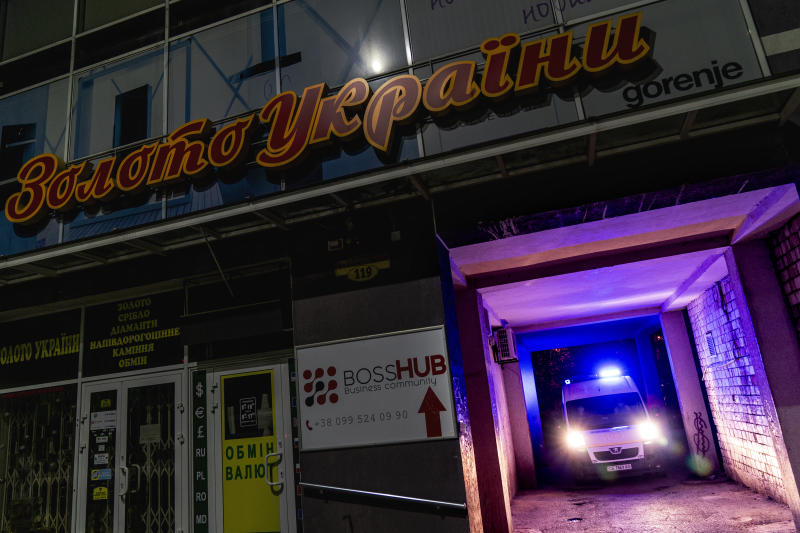 """In this photo taken on Thursday, May 7, 2020, an ambulance carrying a patient with coronavirus leaves the yard of an apartment building with a jewelry shop """"Gold of Ukraine"""", top, in Chernivtsi, Ukraine. Ukraine's underfunded health care system was quickly overwhelmed by the coronavirus, with medics accounting for one fifth of all coronavirus cases in the country.(AP Photo/Evgeniy Maloletka)"""