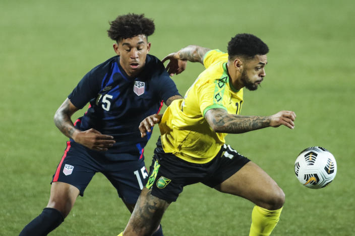 USA's Chris Richards, left, duels for the ball with Jamaica's Andre Gray during the international friendly soccer match between USA and Jamaica at SC Wiener Neustadt stadium in Wiener Neustadt, Austria, Thursday, March 25, 2021. (AP Photo/Ronald Zak)