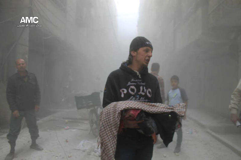 This photo provided by the anti-government activist group Aleppo Media Center (AMC), which has been authenticated based on its contents and other AP reporting, shows a Syrian man carrying the body of a child killed by a government forces airstrike in the Al-Ansari neighborhood, in Aleppo, Syria, Tuesday, April 15, 2014. (AP Photo/Aleppo Media Center, AMC)