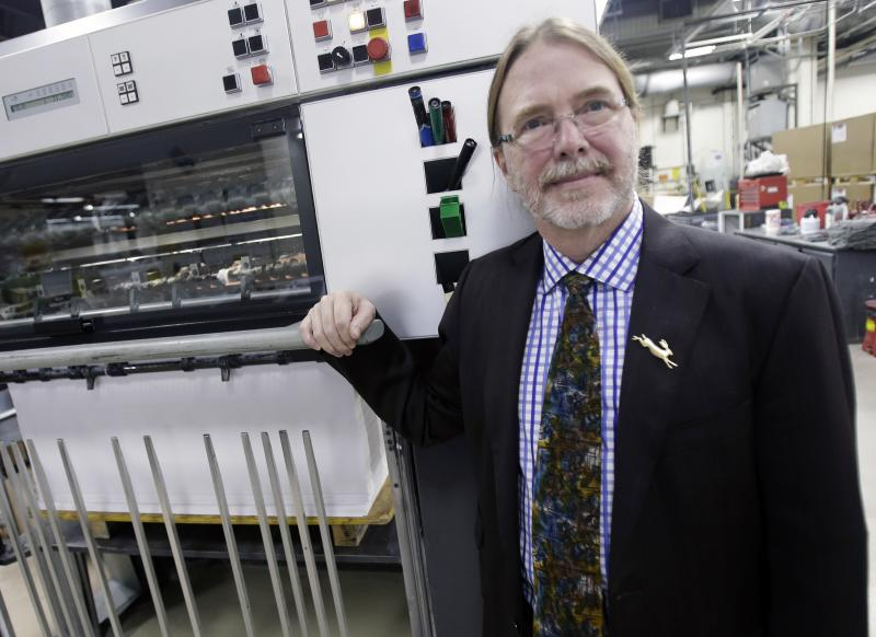 """In this Jan. 30, 2013 photo, printing company owner Dik Bolger poses by one of his presses in Minneapolis. The lifelong Minnesota Democrat who backed Mark Dayton for governor, takes exception to Dayton's plan for new business taxes. """"We're screwed,"""" Bolger said, adding that he is not competitive on a national basis job bid if taxes push him a couple of percent higher. (AP Photo/Jim Mone)"""